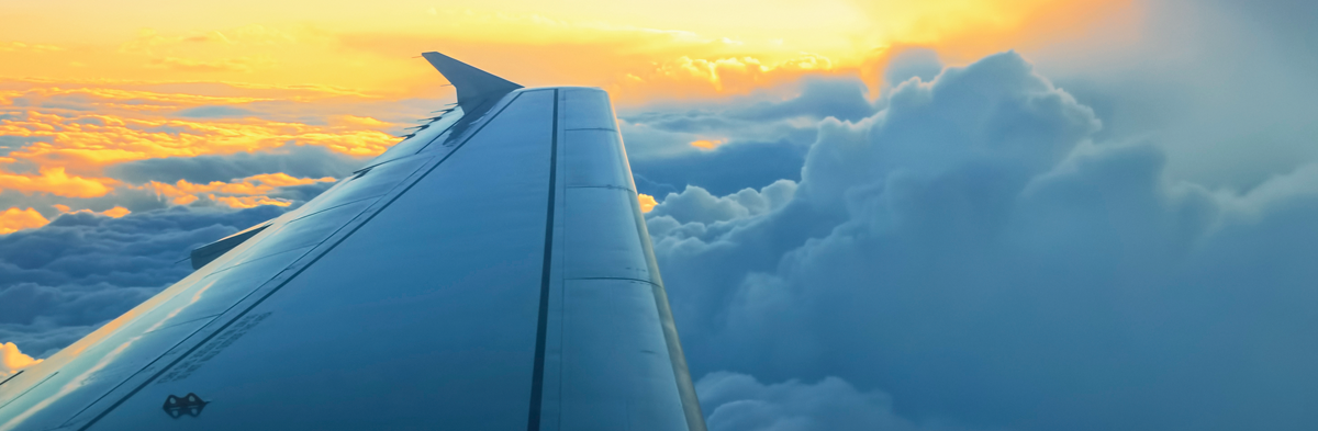 Image of airplane wing and sunset sky